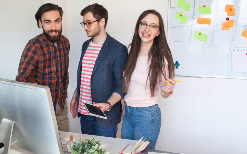 Start-up team of three young hipster guys in modern office collaborating